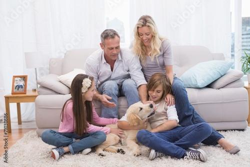 Fényképezés  Smiling family with their pet yellow labrador on the rug