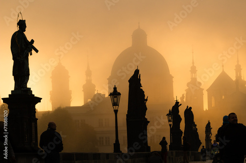 Silhouette of statue and tourists on Charles bridge during sunri Poster