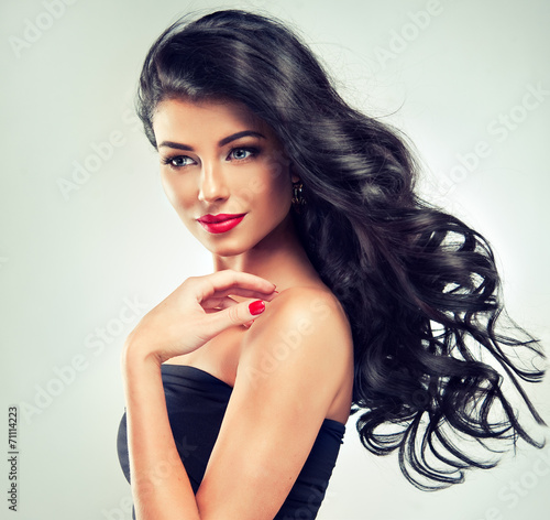 Obraz na plátně  Model brunette with long curly hair