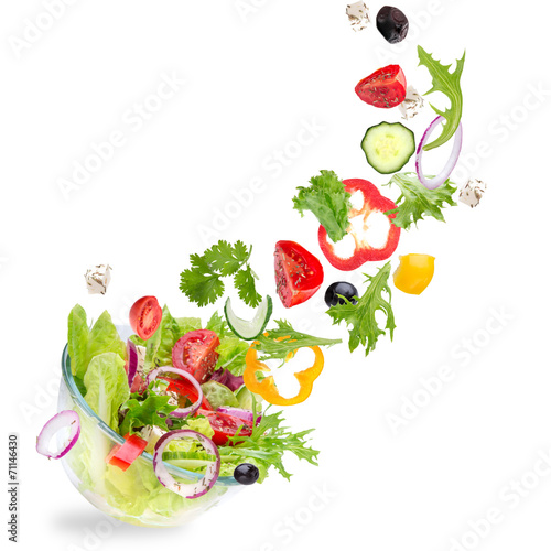 Foto Fresh salad with flying vegetables ingredients