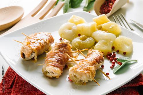 Fotografía  Rollos de tocino, pollo, queso con patatas y cebollas