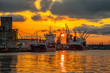 Leinwandbild Motiv Ships and cranes with port warehouse at sunset.