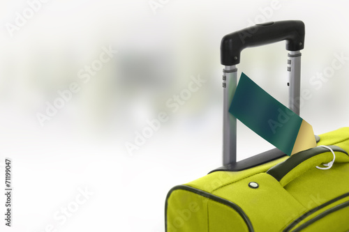Fotografija  Green suitcase with blank label at airport.