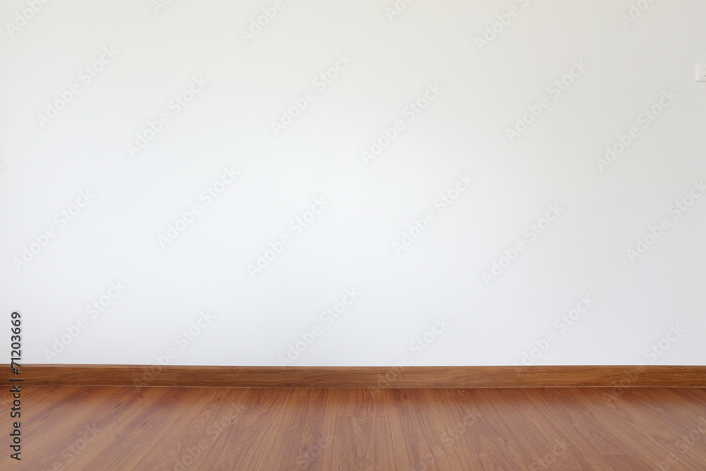 white mortar wall and wood floor in the room