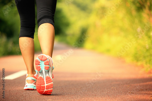 Foto  young fitness woman legs walking on forest trail