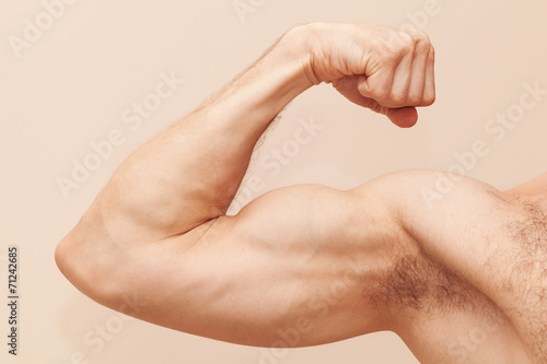 Slika na platnu Strong male arm with biceps. Close up photo