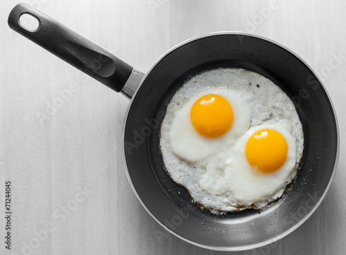 Poster Ouf Two scrambled eggs in black frying pan on white wooden table