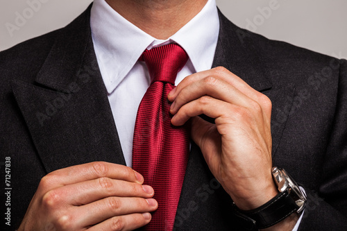 Businessman adjusting his necktie Poster Mural XXL