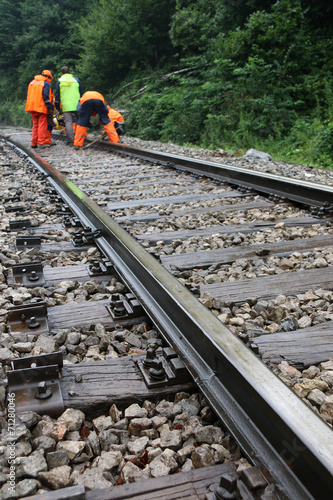 Poster Voies ferrées Workers in orange raincoats repair railroad on rainy day