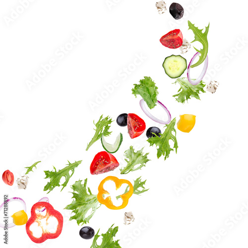 Fotografia Fresh salad with flying vegetables ingredients isolated on a whi