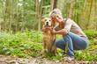 Labrador Retriever mit Seniorin im Wald