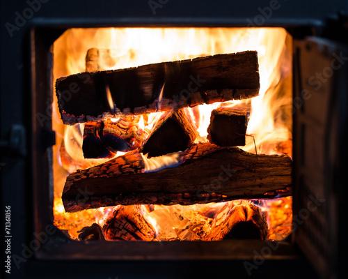 obraz dibond Ein brennender Stapel Holz im Kachelofen