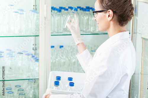 Worker of laboratory putting empty bottle Canvas-taulu