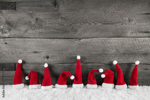 Weihnachtlicher Hintergrund Holz grau mit Weihnachtsmützen rot #71434690