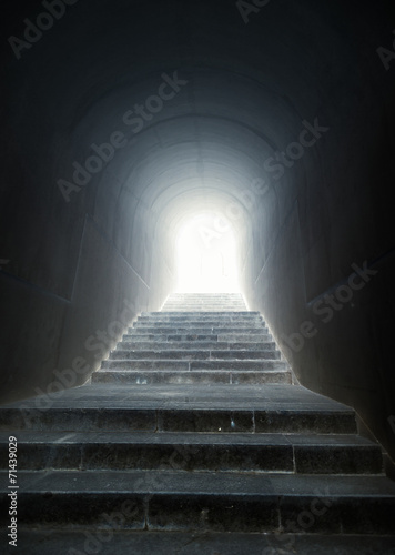staircase in the tunnel with light at the end