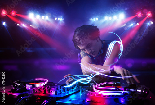 Foto  Disc jockey playing music with light beam effects on stage