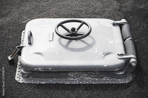 Valokuva  Old gray locked hatch on black ship deck