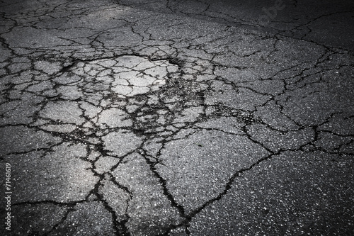 Fotografiet  Dark asphalt road with cracks. Background texture