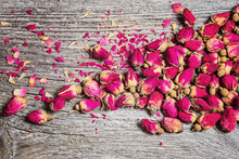 Dry Tea Rose Buds On Old Wooden Background