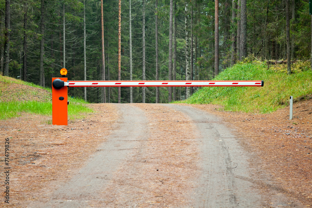 Fototapeta Rural road in the forest with closed red white barrier