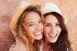 canvas print picture - Two Female Friends On Holiday Together Posing By Wall