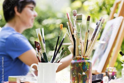 Leinwand Poster Frau malt ein Bild im Garten
