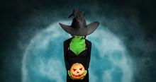 Green Witch Holds Halloween Pumpkin