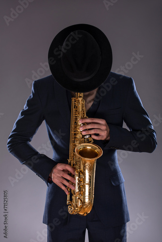 Tablou Canvas Portrait of a jazz man in a suit with a hat hiding his face and