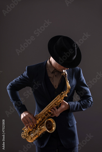 Photo Portrait of a jazz man in a suit with a hat hiding his face and