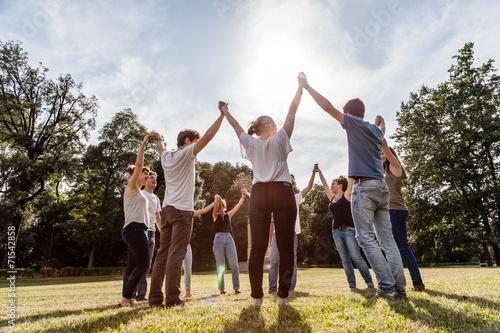 Fotografía  Grupo de amigos en el parque de la mano y se levantan