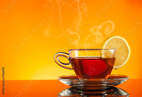 Staande foto Thee Tea in cup with orange background