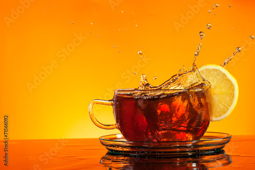 Staande foto Thee Tea splashing out of glass with orange background