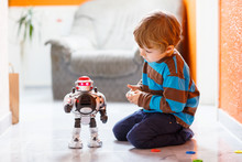 Little Blond Boy Playing With Robot Toy At Home, Indoor.