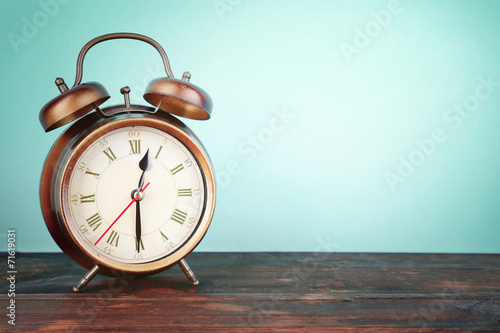 Fotografía  Old alarm clock on wooden table on blue background