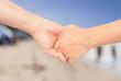 hand in hand with blur beach background