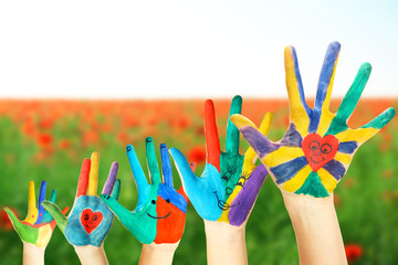 Painted hands on field background