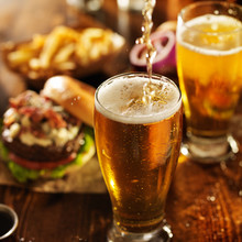 Pouting Beer Into Glass With Burgers On Wooden Table Top