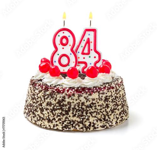 Fotografia  Geburtstagstorte mit brennender Kerze Nummer 84