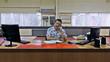 engineer sits at large desk, speaking on phone