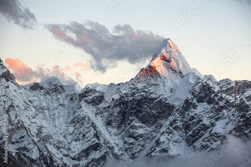 First rays of the rising sun on the top of Ama Dablam peak Poster