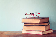 Old Books With Vintage Glasses On A Wooden Table. Retro Filtered