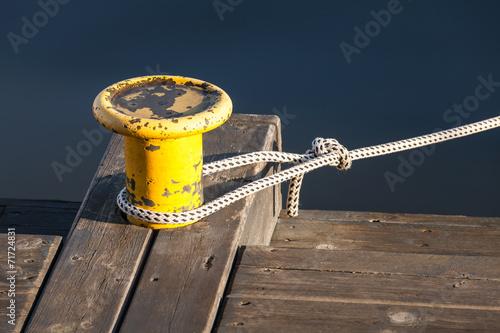 Yellow mooring bollard with nautical rope on pier Fototapeta