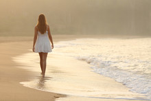 Woman Walking On The Sand Of T...