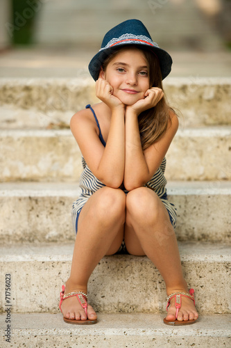 Cute young girl with hat sitting on stairs in park Wallpaper Mural