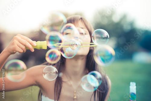 Obraz na plátně Krásná mladá žena s bílými šaty foukání bublin
