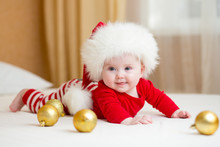 Funny Santa Baby Girl Lying On White Bed