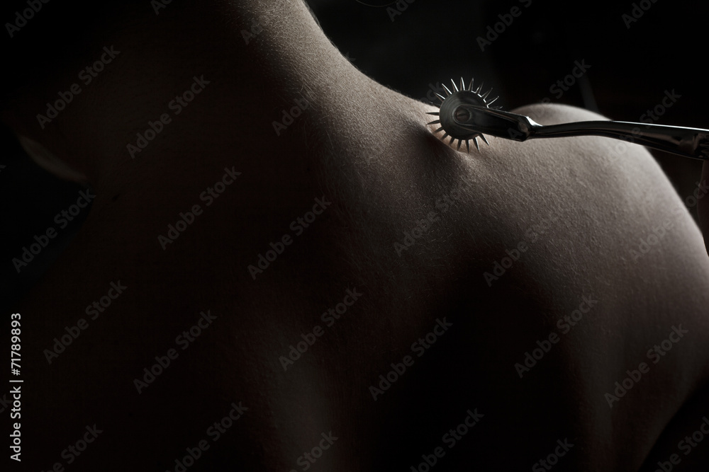 Fototapety, obrazy: Nude submissive woman shoulder, bdsm act with Wartenberg wheel