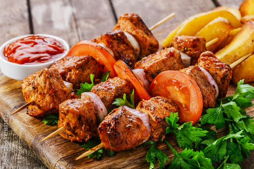 meat skewers with potatoes on the board - 71833872