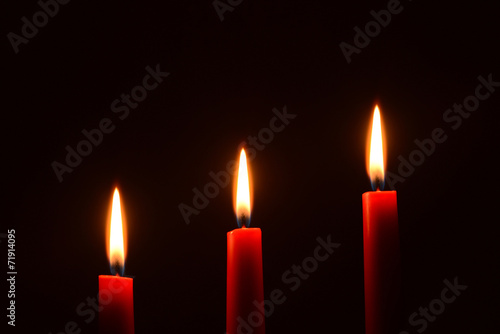 Fotografia  Three red candles on a black background