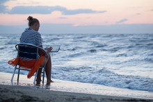 Woman Sitting On Chair By Sea And Using Pad